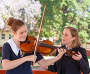 One msic teacher mentoring one glennie girl how to play violin